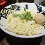 麺屋武蔵 鷹虎 - 麺の上には黄身がとろりとした半熟煮玉子が乗っており