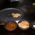 六本木モンシェルトントン -  お皿の上の焼いたニンニクと、ステーキのたれです。