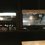 53942256 - 厨房はあちら。客席から見えるところにお酒も並べてあります。