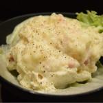 東京餃子 あかり - ベーコンといぶりがっこの燻ポテトサラダ@480円。スモーキーな薫りが良い塩梅。開幕に。