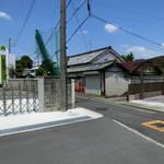 仲島 - 県道から一本入った所。画像右手のカーポートとシャッターの閉まったお宅の間の狭い路地を右方向に入っていく。車で入って行かないように!