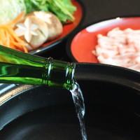 悠久乃蔵 - 日本酒を一升瓶から豪快に鍋に注ぎ入れます。日本酒の旨味と栄養をそのまま食します。