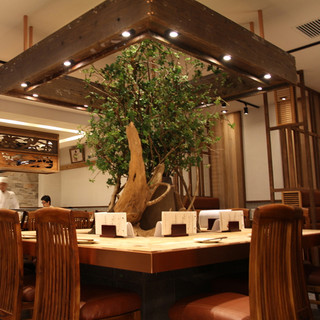 緑のある大きなテーブルを中心とした、温かみある空間