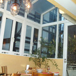バール・メロン - 自然光が差し込むサンルームのテーブル席。明るくてお洒落な店内です。