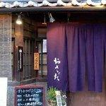 おさだ - これがお店の入口です。 暖簾がいい感じですね。 紫色にシンプルに おさだ と白抜きで書かれています。 屋根上には木彫りで おさだ と。 そして、きりん生ビールの達人の店のプレートが掛かっています。