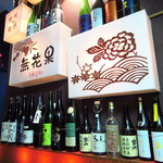 男前料理と五島列島直送の魚 神楽坂はずれ 無花果 - 店舗看板、その横にはプレミアムな酒の空瓶が置かれている