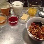 55752101 - パンのプレートが来る前にセルフで集めたものたち(牛乳・オレンジジュース・ジャム2種・バター・グラノーラ・ヨーグルト)