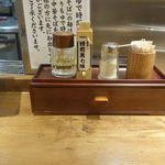 舎鈴 - この日は担々麺590円を注文。しばし箸置き場や、焙煎黒七味の姿を見て待っていると