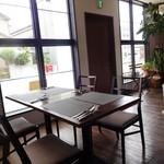 "Le 4 Stagioni Italiane ""IL PARCO"" - 入口からすぐのテーブル席。テーブル間を広く取り、大きな窓で 明るく 開放感のある 店内。"