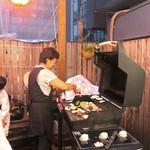 さくら - 笑顔で栄螺と野菜を焼くママ
