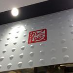 どうとんぼり神座 - 厨房の上のロゴマーク。全体にメタリックなアクセントを多用している店内デザイン。
