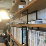 アーキ ジェイ カフェ - 店内 建築関係の書籍が並ぶ書棚の上には建築模型が飾られている。