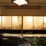 キのや - カウンター背側の間接照明に浮かぶ絵(2016.9.22)