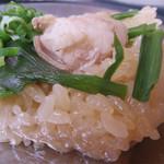 中洲二丁目屋台 - モツ鍋スープ(醤油味)で下ごしらえしたおこわに、モツ・ニラ・唐辛子・ニンニク・ネギをトッピングして、                             蒸し上げたものです。
