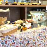 デイリーズ マフィン - 棚の上にマフィン、下のテーブルには焼き菓子が。
