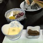 竹内 - お通しの玉子豆腐とコンニャクの煮物、奥にはおにぎりと漬物