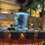 パシフィカ - カウンター席の中央に熱帯魚が泳ぐ円筒型の水槽