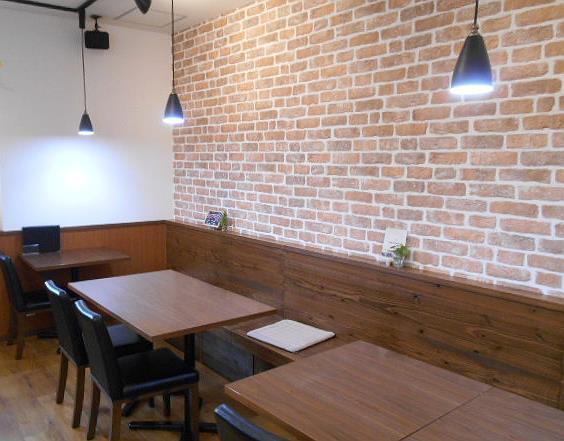 カフェ・ベッラメンテ - 内観:店奥の壁は煉瓦で統一 広めのテーブル