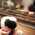 牛串萬の - ボキらが座った席からは カウンター内で焼きものをしているところがよく見えます。 ちょうどボキらが注文したものが焼かれてるところだよ。  ちびつぬ「煙がモクモクしてるわね~」