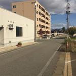 57860383 - 店の前から駐車場のある茶色のマンションを見た画                       50m弱の距離があります                       34〜38が当店の駐車スペースでした