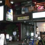 秋津日本酒居酒屋 しば田 - 武藤ビル。向かって左手はパチンコ店。黄色い看板の下の通路を奥へ