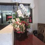 家庭食堂 おおきなかぶ - カウンター席にもお祝いの花が。