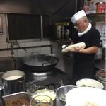 華隆餐館 - 麺を鍋に削り入れている