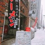 拉麺 札幌ばっち軒 - ビルのエントランスに幟と看板