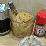 天丼てんや - 天丼てんや 西葛西店 卓上に置かれる大根の漬物と調味料類