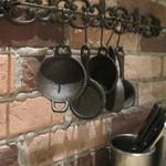 トゥッカーノグリル&バー - 厨房に吊るしてあるフライパン