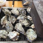 島田水産 - どんどん牡蠣を投入します 隣の缶でふたをします