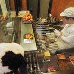 おせんの里 松屋 - こちらは伏見稲荷名物・稲荷煎餅のお店なんだ。  ちびつぬ「お煎餅を焼いてるところが見られるのよ~」  機械じゃなくて、一枚一枚手で焼かれているんだね。