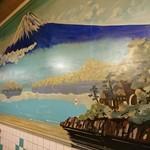 やまとや - 銭湯をイメージした富士山とタイル貼りの壁。