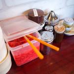 元祖糸島ラーメン 銅鑼 - 卓上の調味料。辛子高菜と激辛モヤシはセルフで用意されています。