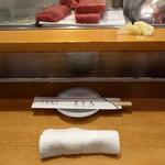 61759786 - お絞りと割り箸、醤油皿。お店は狭い中外人さんが多いので更に狭さを感じる。