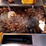 肉の丸勝 - 店頭の鉄板でホルモン焼き