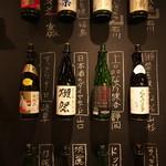 かいえん 海鮮と日本酒の専門店 - 今まで取り扱った日本酒を壁に飾ってあります。