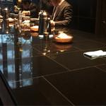 港屋2 - 店内は黒い石貼りの大テーブルで立ち食いです。
