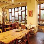 ムモクテキカフェ - 広々としたイス席。お一人様には緑溢れる中庭に面したカウンター席がおすすめです。