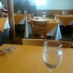 タベルナ イル ロカーレ - 黄色いテーブルクロスと窓から射す陽光で明るい綺麗な店内