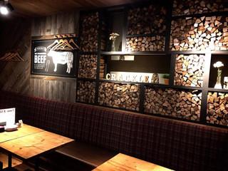 薪焼き肉バル Crackle - 壁には薪がぎっしり敷き詰められていてお洒落