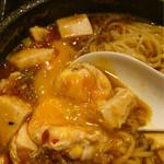 65514712 - 石焼鍋で熱々の麻婆麺に卵黄をからめて頂く