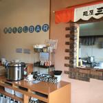 麺屋三郎 - 番号札で呼ばれると右側のカウンターで受け取り。 セルフコーナーにはもやしやご飯、調味料が置いてあります。