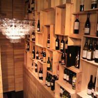 ヴィノシティ - 入口にはワインが並び、ワイングラスで出来たシャンデリアが目を惹きます!