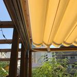 66282390 - クリーム色のシェードが日差しを和らげてくれているテラス席。