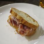 エロうま野菜と肉バル カンビーフ - イベリコ豚の生ハムをお通しの「峰屋」のパンにはさんで