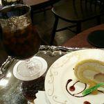 66491246 - アイスコーヒーとロールケーキ