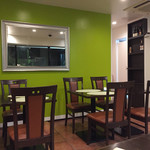 オリエンタルキッチン アンジュナ - グリーンの壁が素敵。椅子とテーブルの茶色とのコントラストがいい。