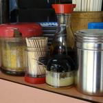 67077200 - 「博龍軒」高台に置かれたコショウ・ゴマ・ニンニクペースト・塩・醤油・ラーメンのタレなど