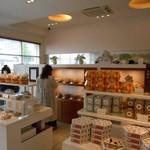 グラン ダ ジュール - 焼き菓子棚の向こうがカフェスペース